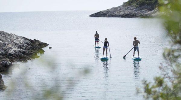 Drei junge Menschen paddeln mit ISUPs an der Küste entlang.