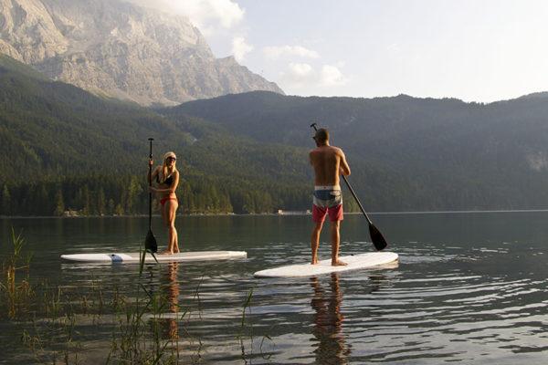 Junges Paar ist mit Boards von TRIPSTIX auf einem See unterwegs