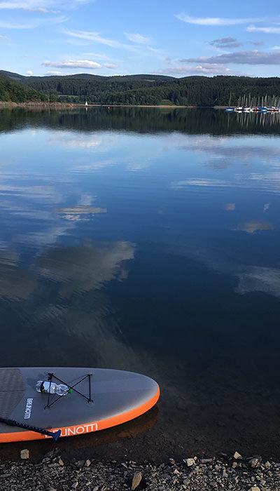 Das grau-orangefarbene ISUP am Ufer eines Sees